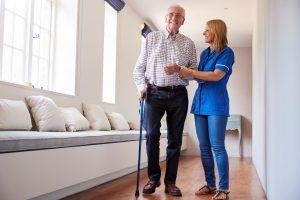 Sairaanhoitaja auttaa vanhusta kävelyllä