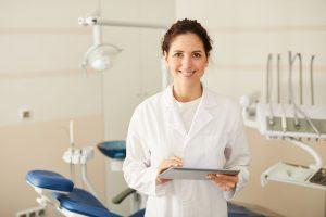 hammaslääkäri hymyilee vastaanotolla