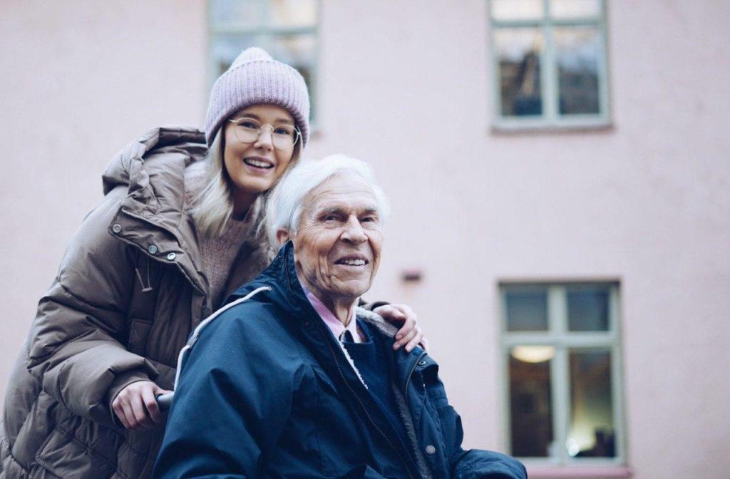 Hymyilevä ikäihminen ulkoilee Gubben kanssa.